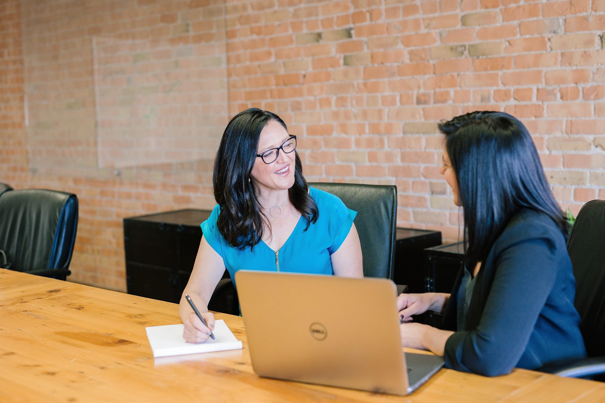 Two women talking by a desk
