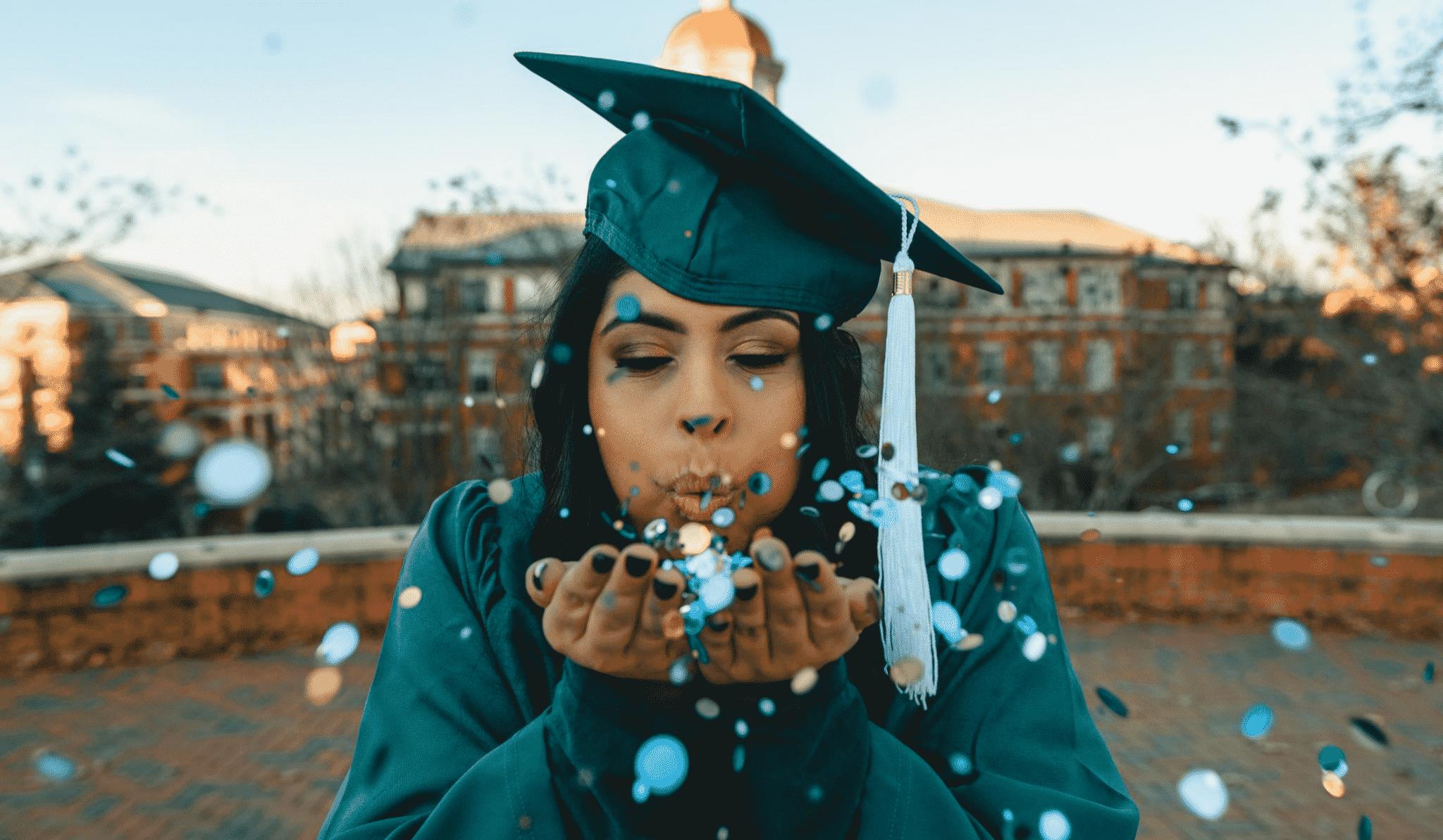 a female graduate blowing confetti