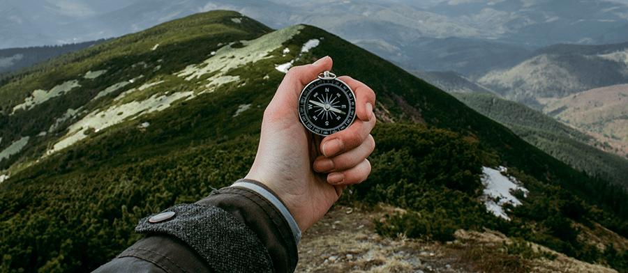 man's hand holding compass
