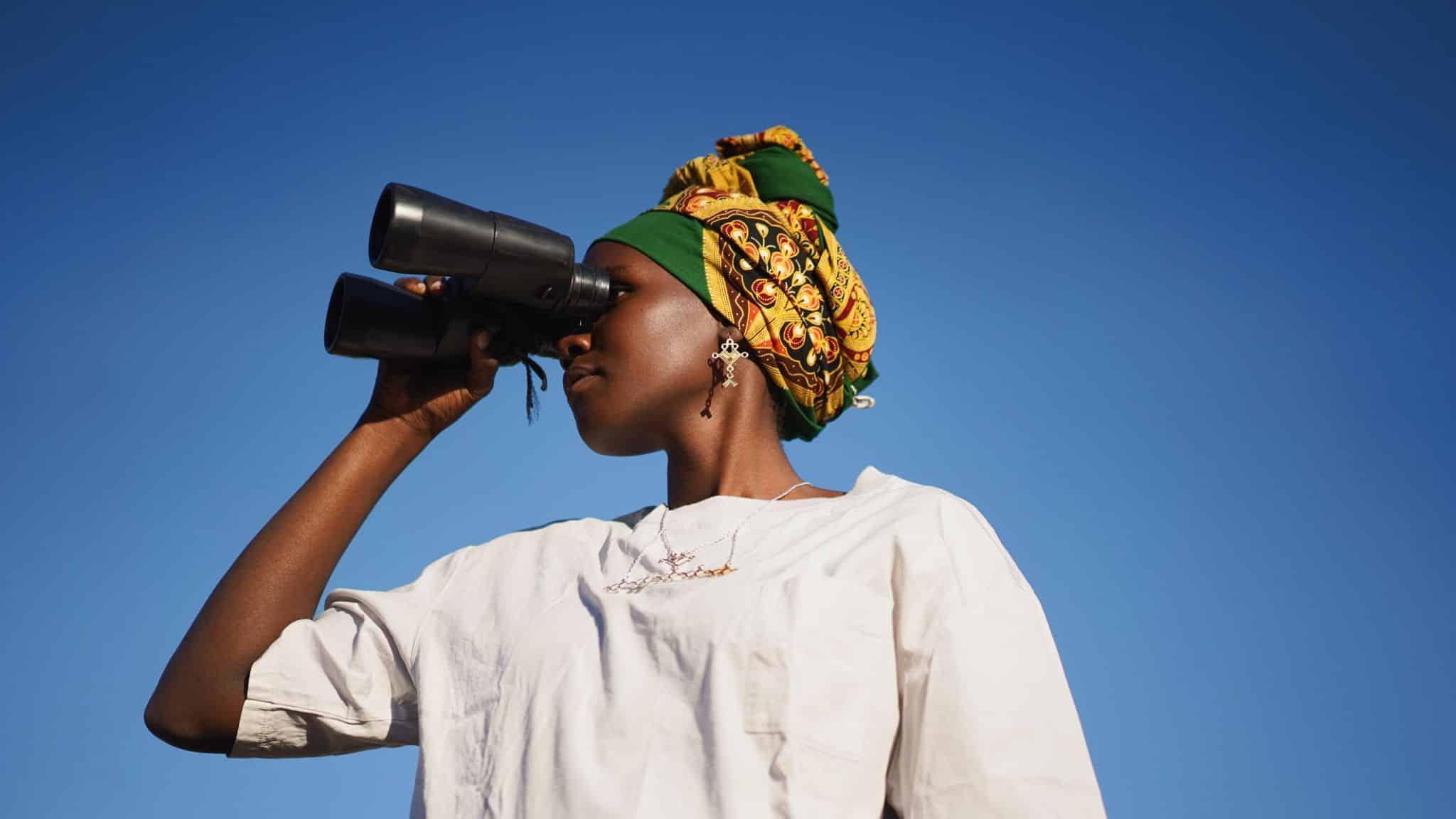 woman looking through a binocular