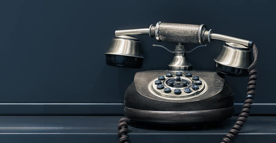 Old-fashioned rotary telephone against blue background