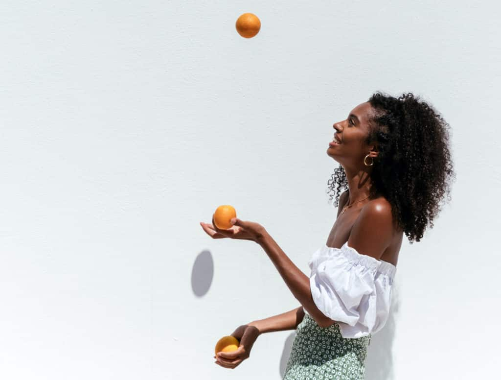 Side view of happy young Black woman in summer outfit juggling with ripe oranges against white wall in sunny day Side of a smiling African American female in summer outfit juggling oranges against white background on a sunny day,